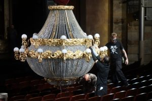 """Staff adjusts the chandelier prior to showtime.""  Photo by Tom Jones."